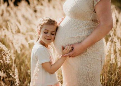 dziewczynka przytulające brzuch swojej mamy w ciąży
