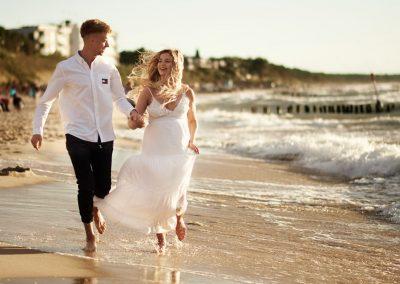 sesja ciążowa nad morzem rodziców biegnących wzdłuż plaży w mielnie