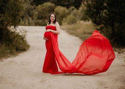 sesja ciążowa w plenerze, przyszła mama ubrana w czerwoną suknie na tle drogi