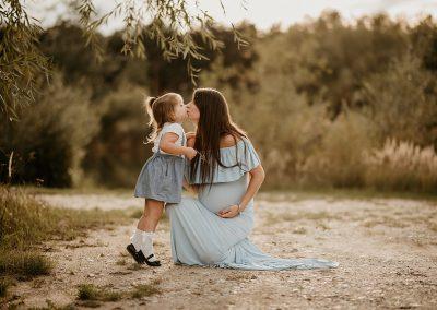 mama i córka obejmujące się na sesji ciążowej w niebieskiej sukni ciążowej na plaży