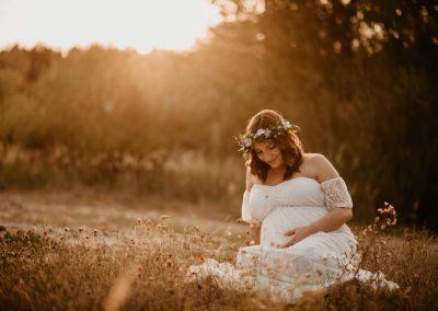 przyszła mama na sesji ciążowej siedząca w białej sukni na łące przy zachodzącym słońcu